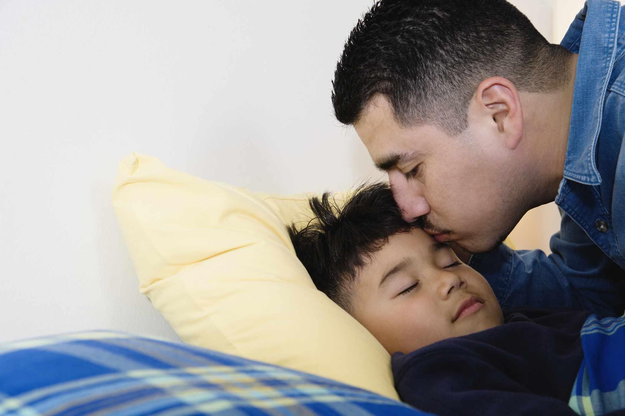 Dad kissing son goodnight