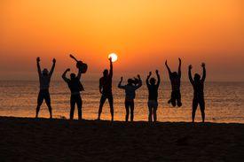 Friends having fun on beach at dawn