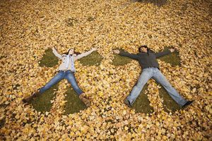 Happy people making angel forms in fall leaves