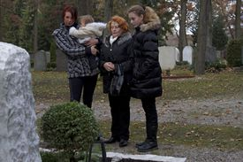Multigenerational family visiting gravestone in cemetery