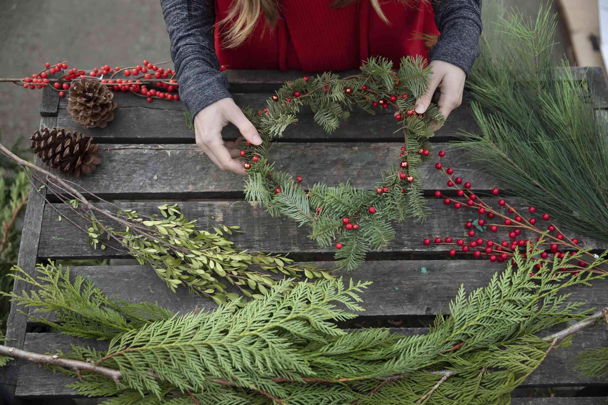 Woman making Yule wreath with berries and branches
