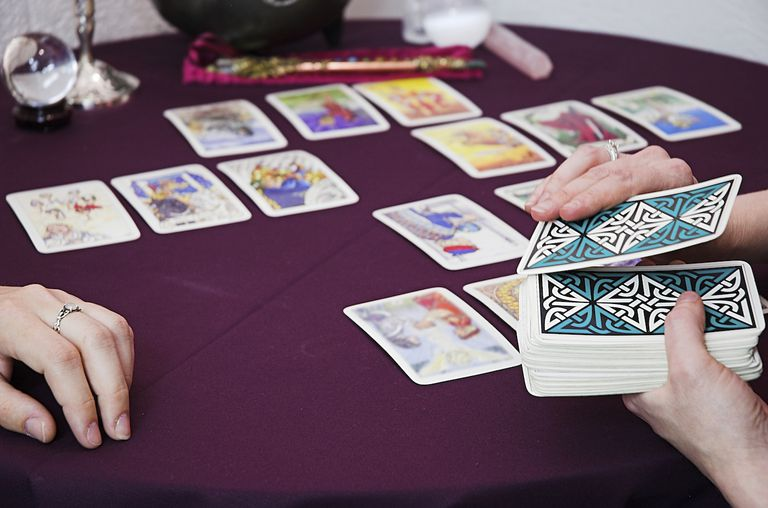 Closeup of cards and reader's hands during a Tarot reading