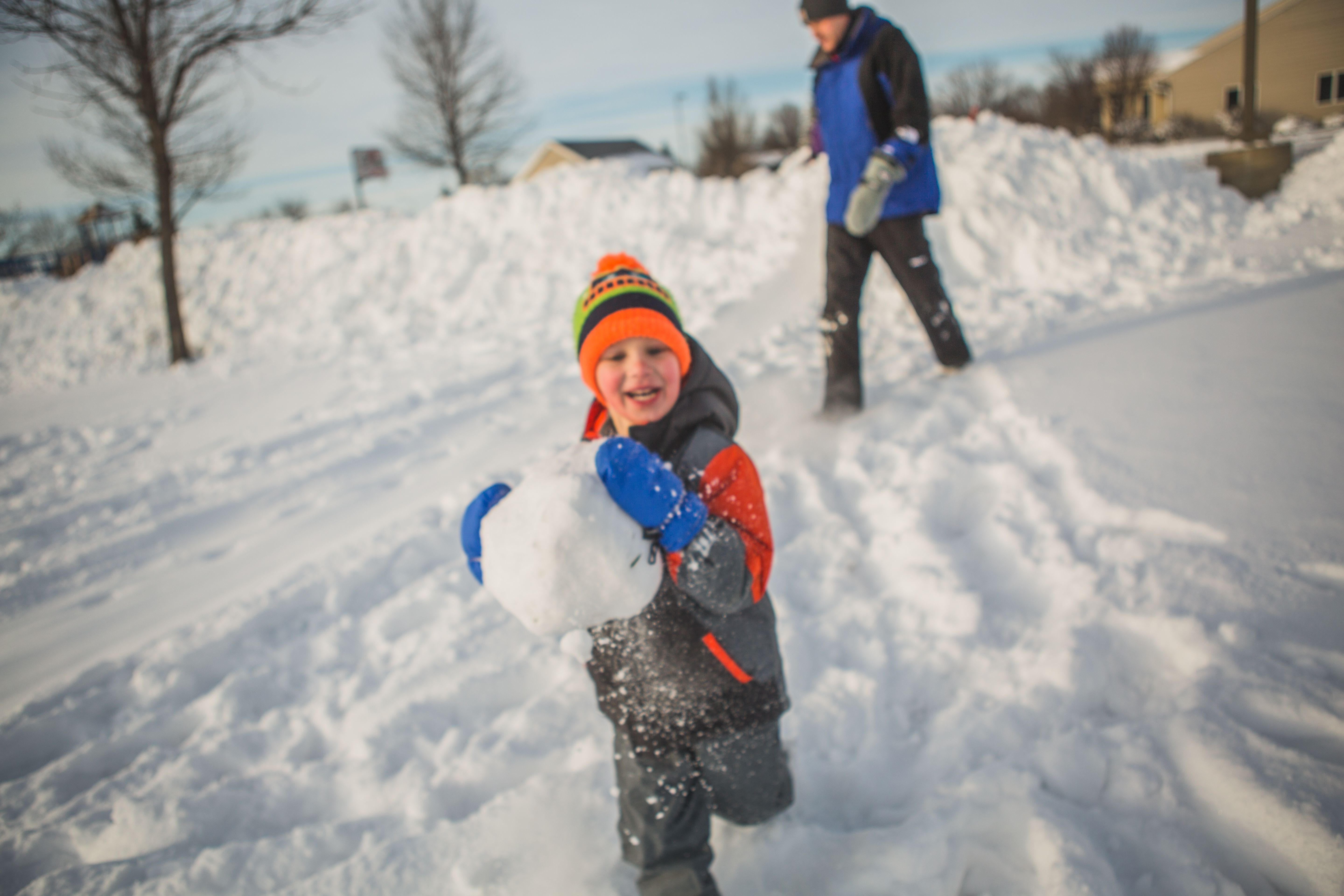 Boy Running With Giant Snow Ball