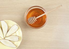 Slices of apple with a honey jar