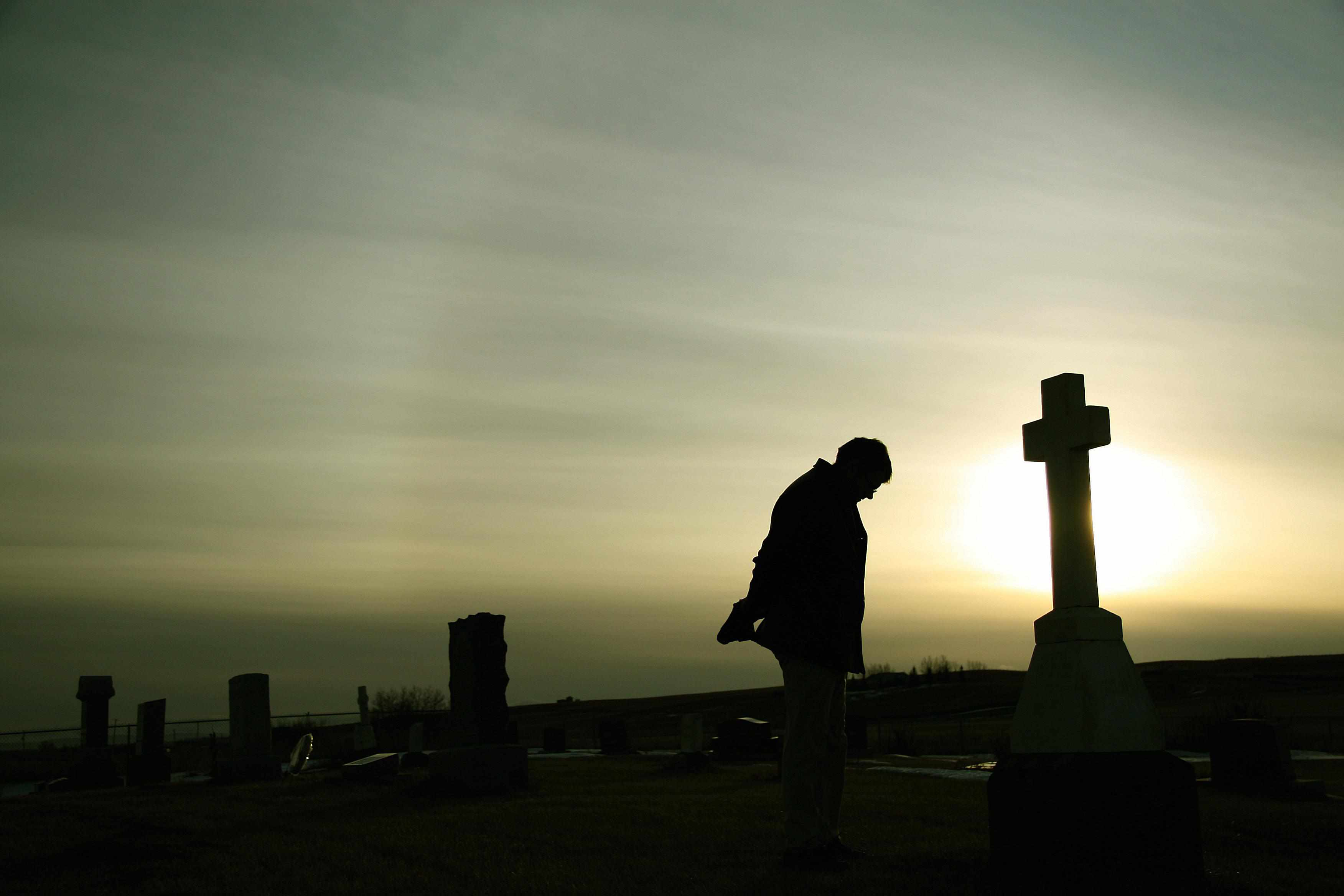 Man mourning in a graveyard.