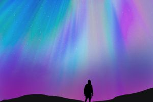 Silhouette of a guy with the beautiful colorful northern lights falling from the sky in Iceland in a stunning clear and nice lights with the sky full of stars. Aurora borealis.