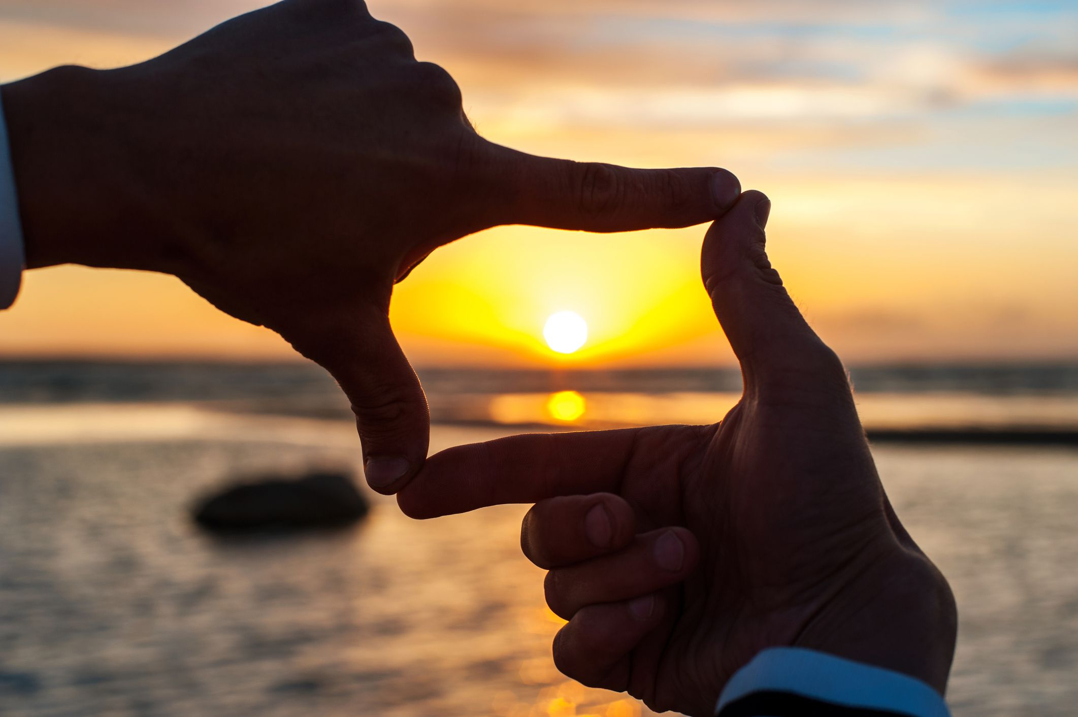 Man looking through fingers at sunset