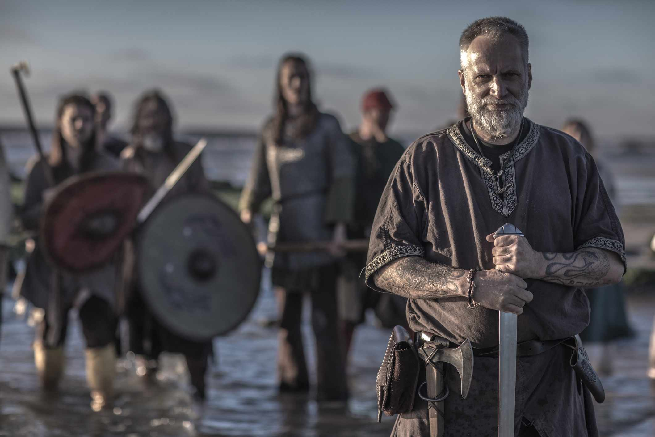 A individual viking warrior in front of a hoard of Weapon wielding warriors in the sea