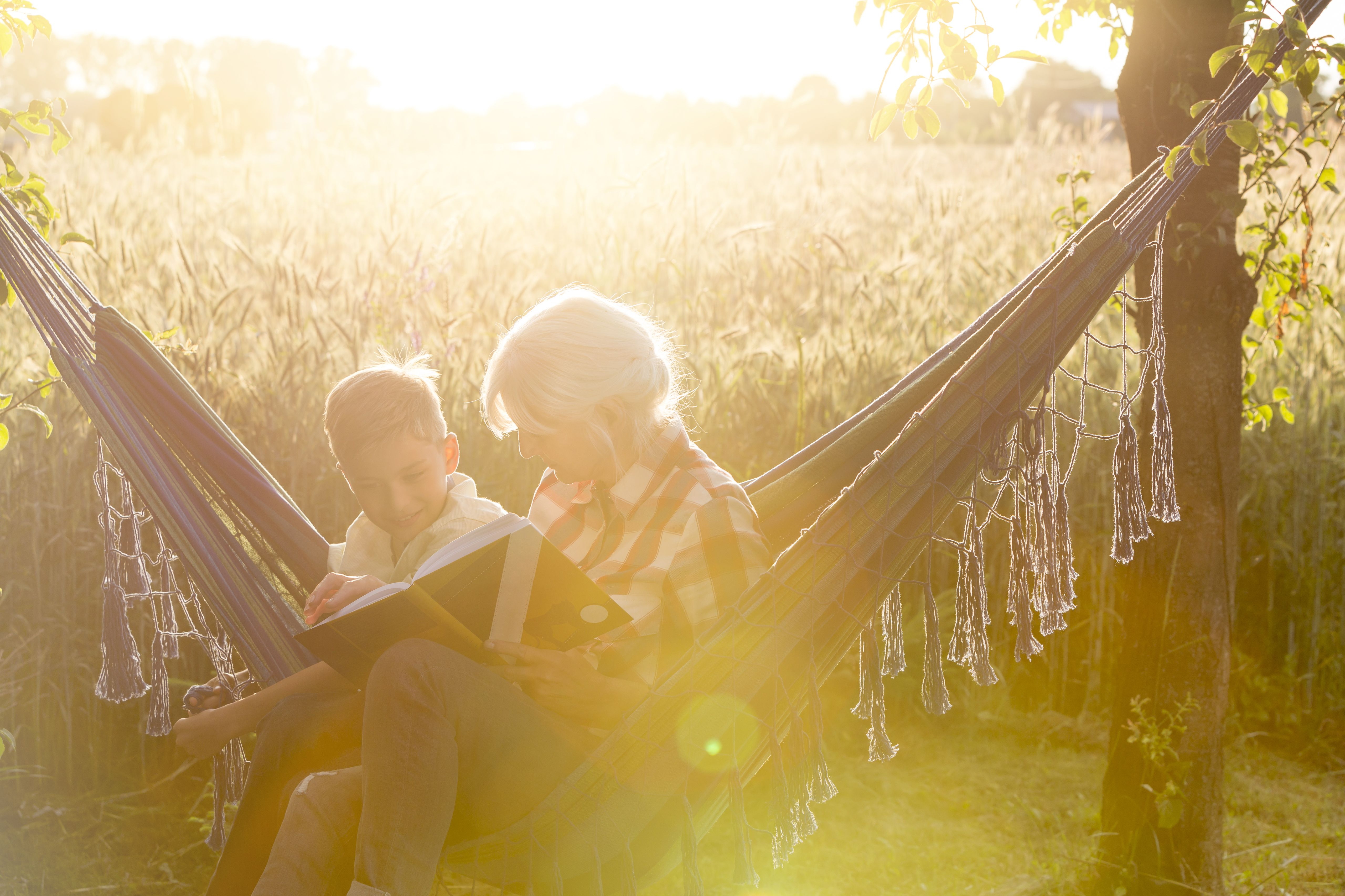 Grandmother and grandson reading book in sunny rural hammock
