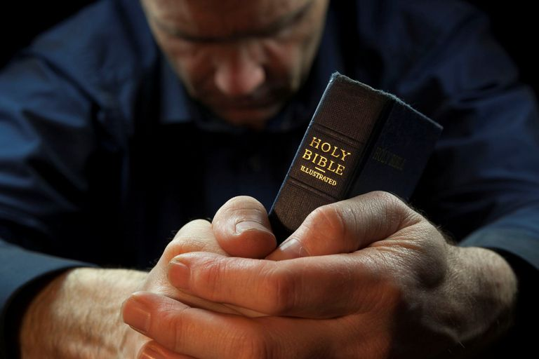 Man praying while holding a bible