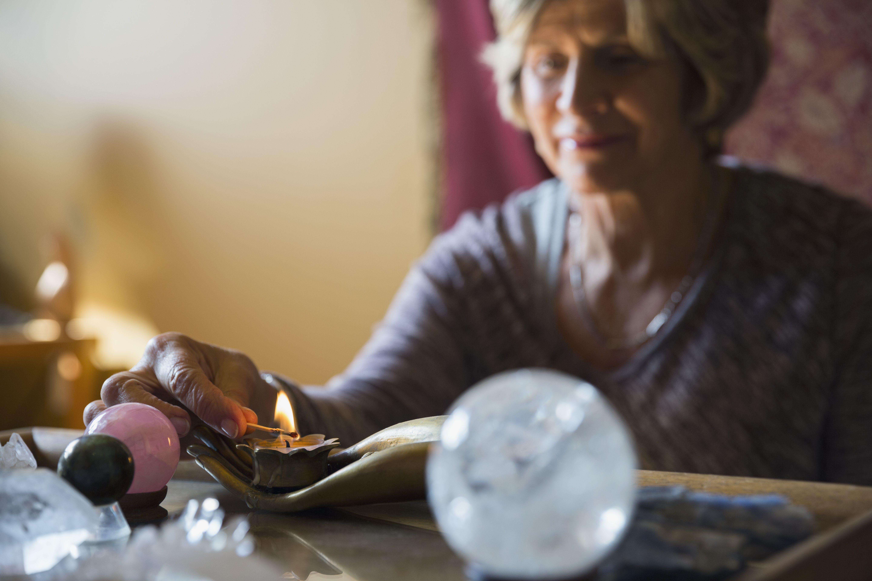 Senior woman lighting candle for meditation