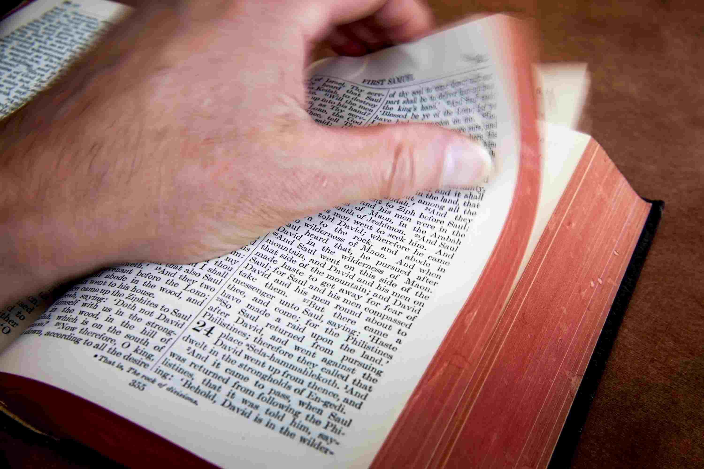 Man thumbing through a Bible