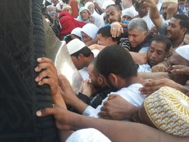 Muslim people trying to reach the Black stone on Kaaba in Mecca