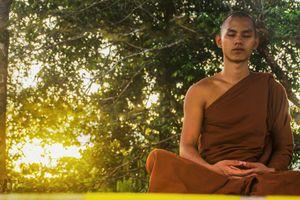 Young man wearing robes meditating outdoors.