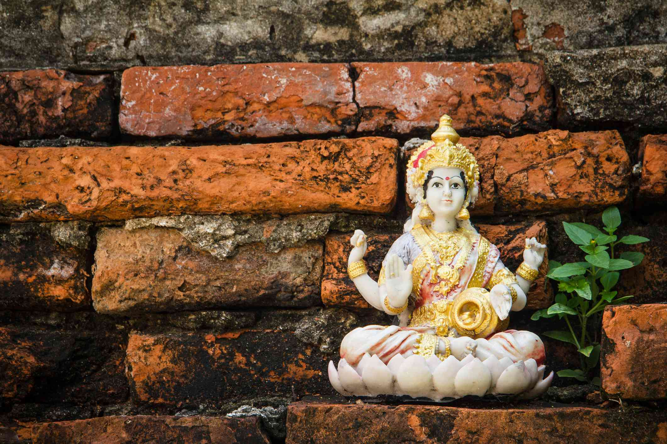 Close-up Of Laxmi Statue Against Red Brick Wall
