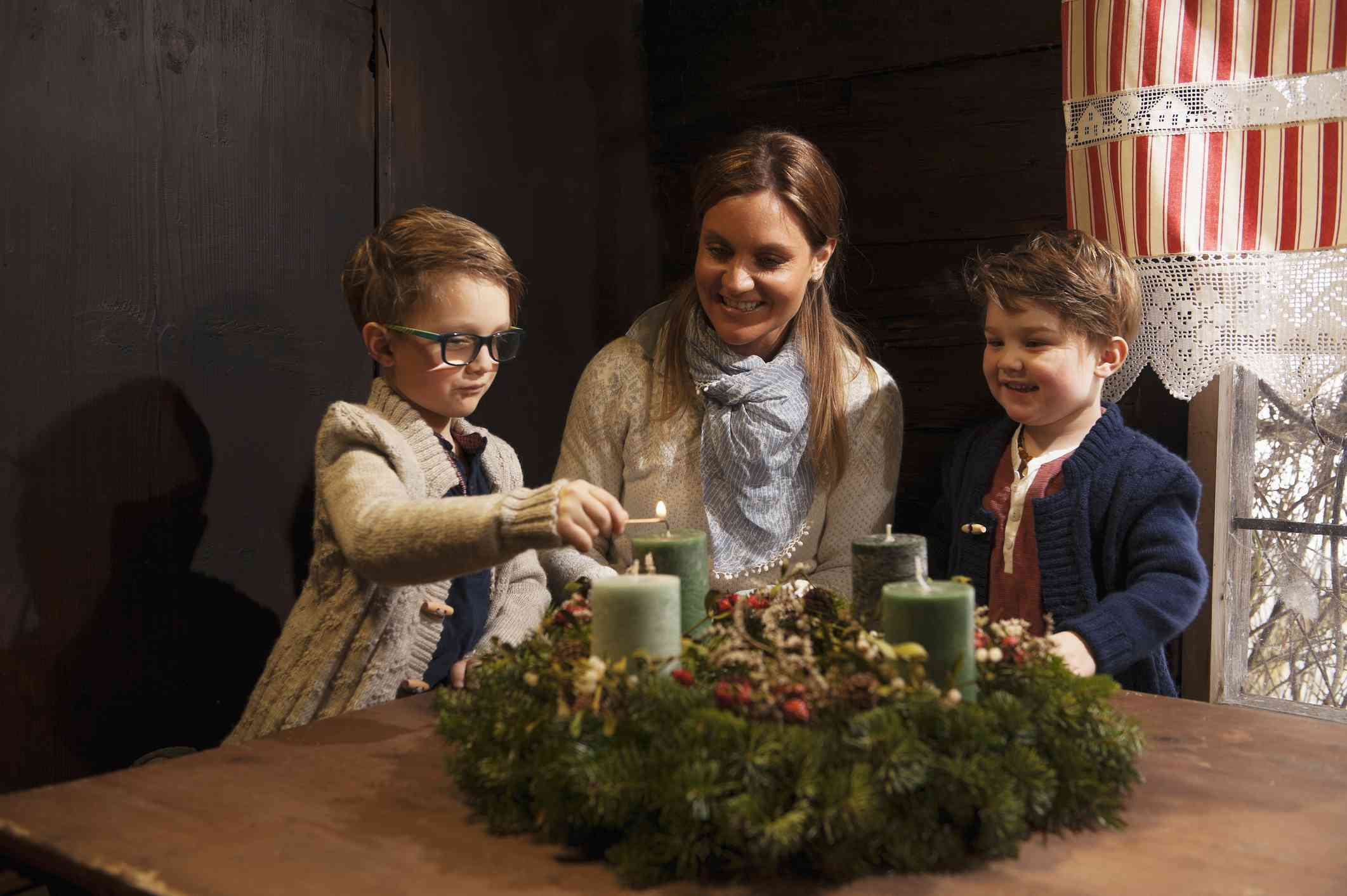 Woman and her sons lighting advent candles.