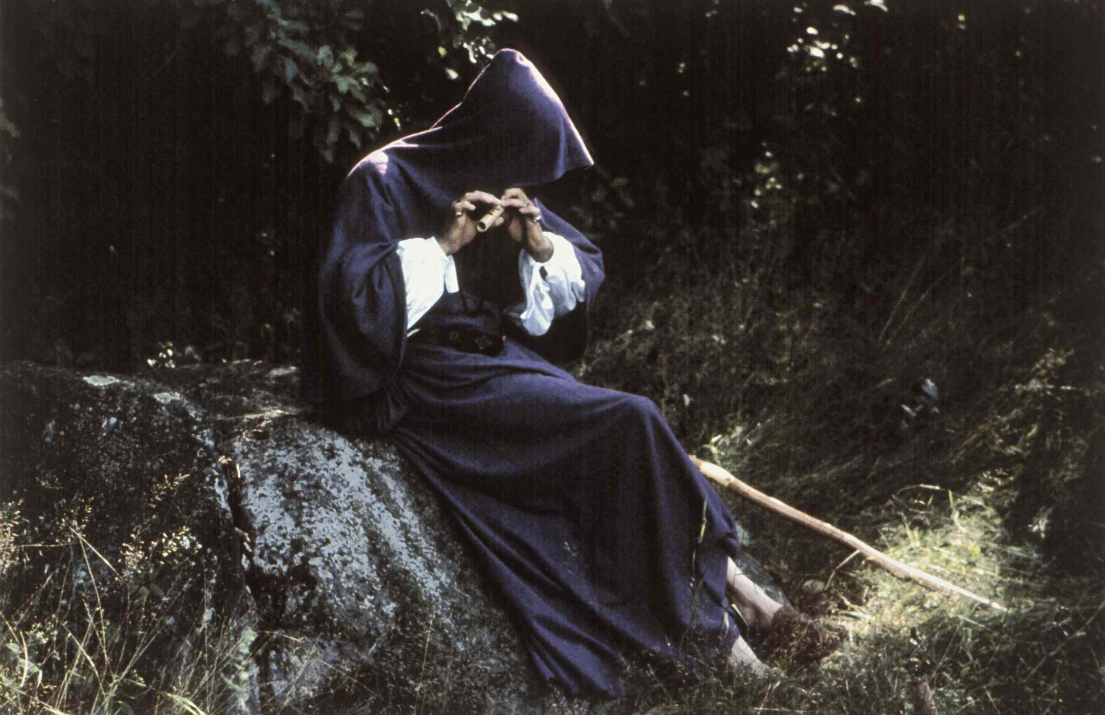 Person in hooded robe playing flute in forest
