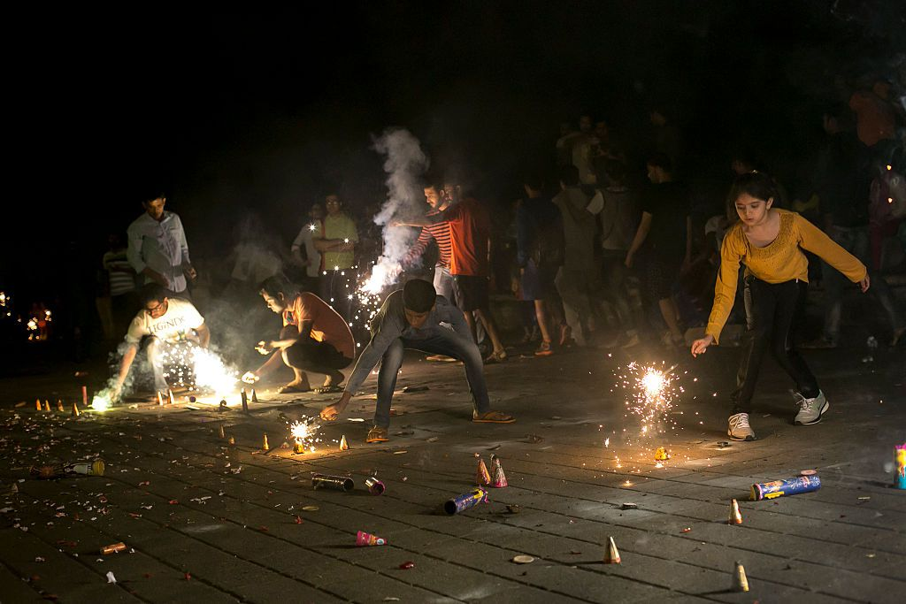 People light fire crackers as Indians celebrate the annual festival of Diwali on October 30, 2016 in Mumbai, India.