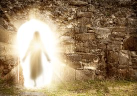 Easter resurrection—silhouette of Christ, bathed in light, emerging from stone tomb.