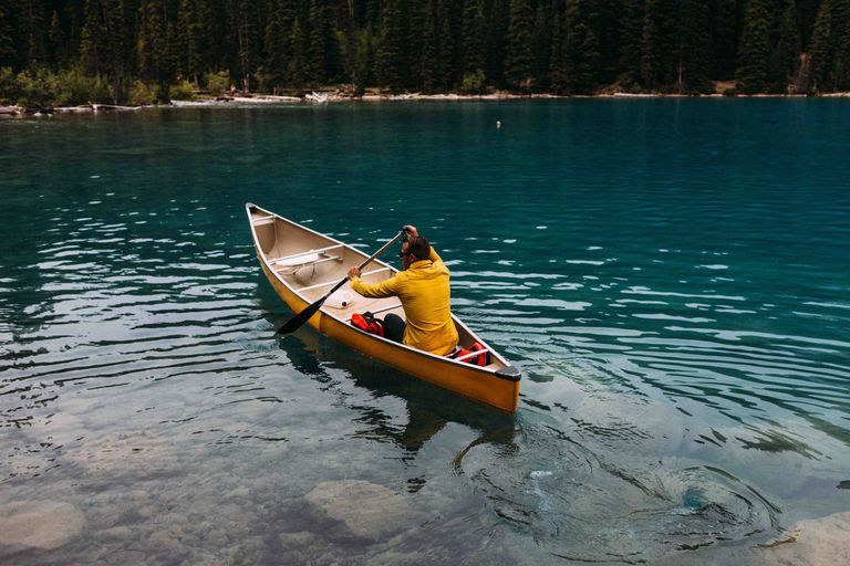 High angle rear view of mid adult man paddling canoe on Moraine lake, Banff National Park, Alberta Canada