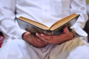A person reading the qu'ran.
