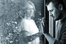 man holding hand up to window with ghost on the other side