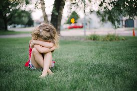 little girl looking distraught in grass