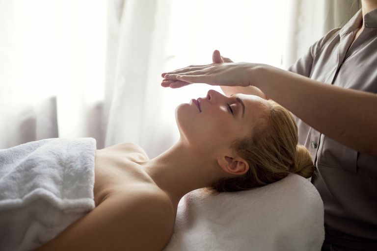 Midsection of therapist giving Reiki treatment to woman on face at spa