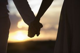 Mature couple holding hands at sunset, close-up