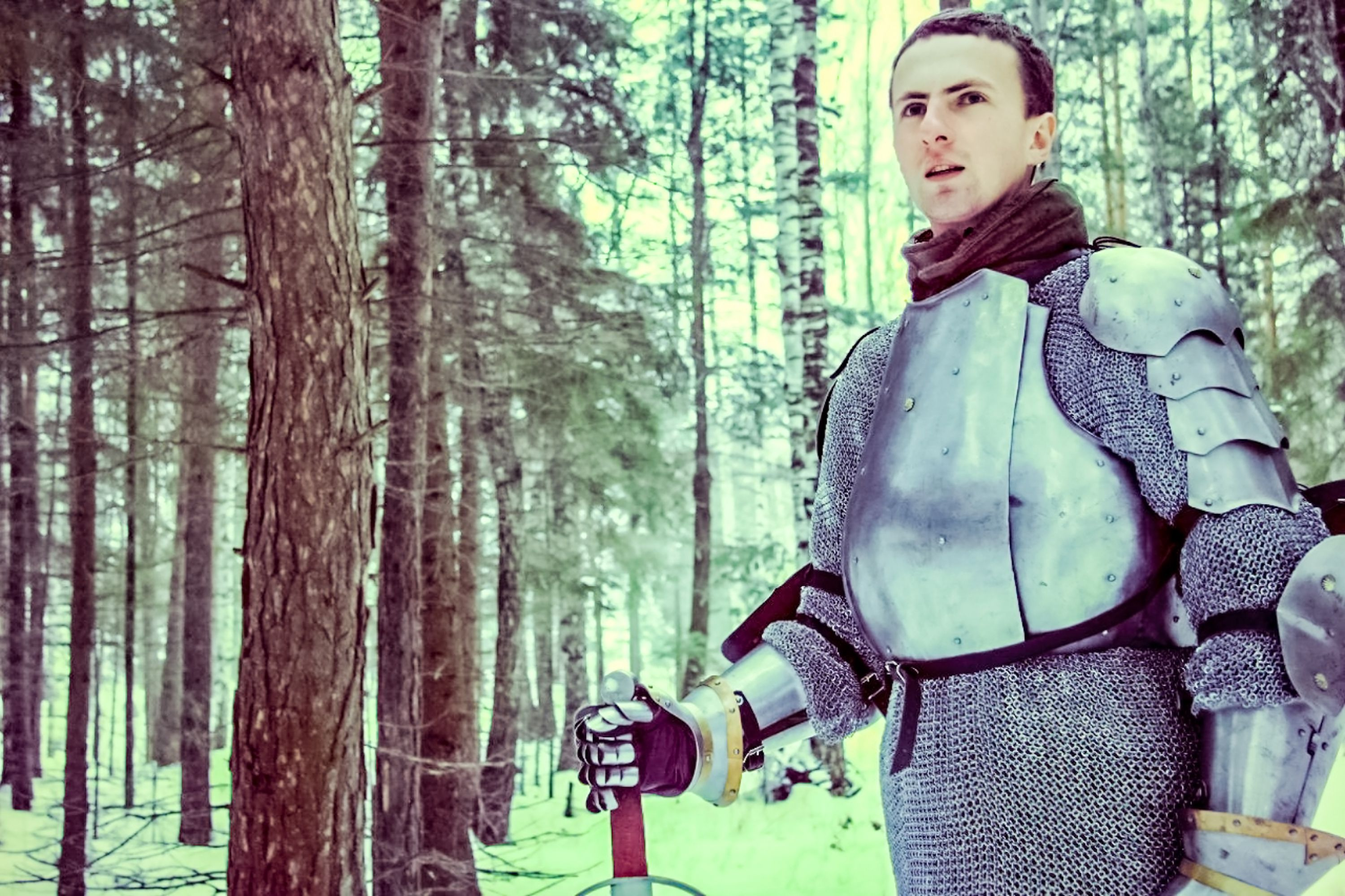 Knight in armor and with a sword in the middle of a winter forest. Vintage military uniform