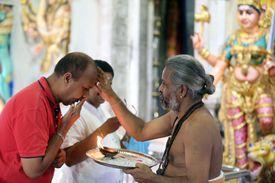 Hindu Brahmin priest applying tika during a morning prayer or puja.