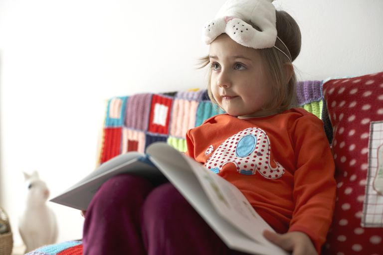 Girl with bunny mask with a picture book in her lap