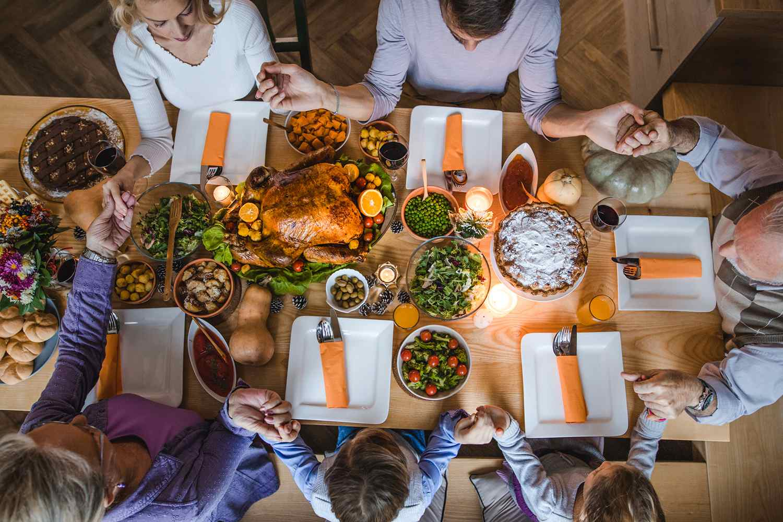 Extended Family Saying Grace Before Thanksgiving Dinner.