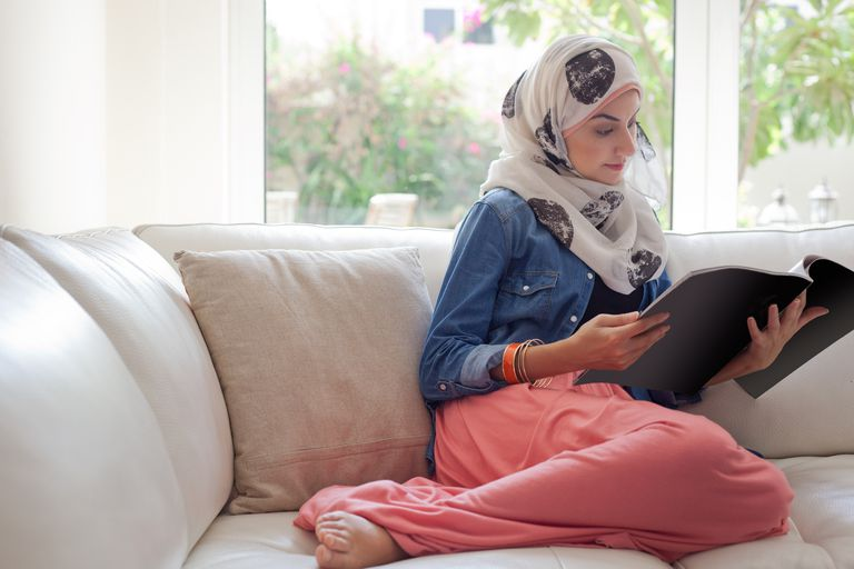 Arab woman reading a magazine on the sofa.