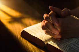 hands folded together resting on an open bible