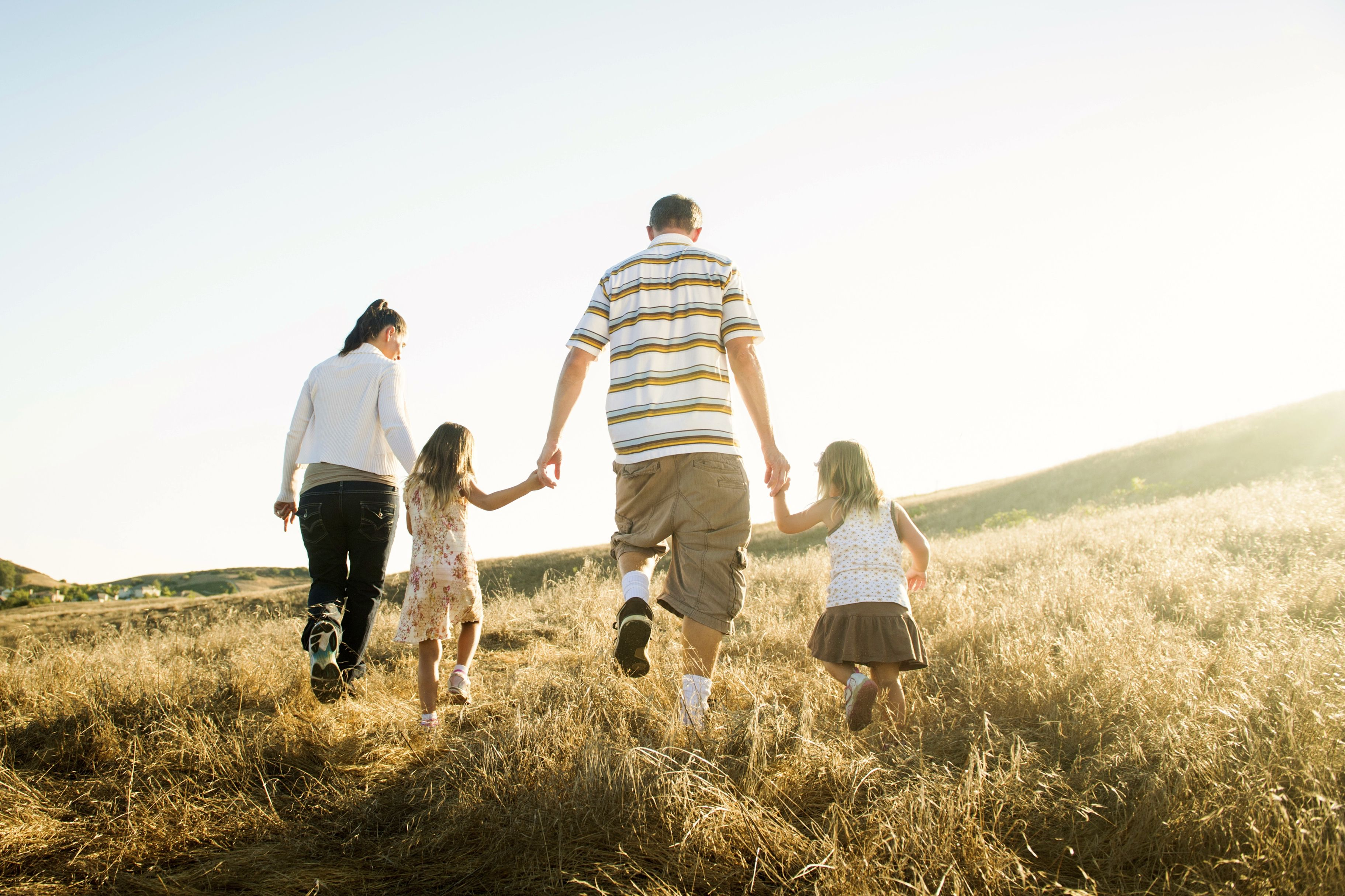 family walking through meadow holding hands