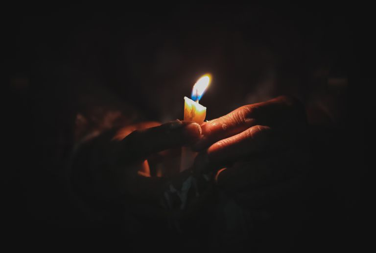 Hand Holding Illuminated Candle