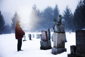 A man in a cemetery in winter.